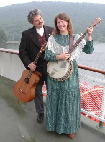 photo of Dave Para holding a guitar, and Cathy Barton holding a banjo