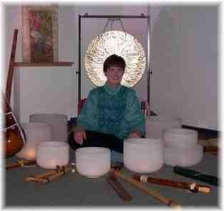 photo of Rahbi Crawford sitting surrounded by 8 crystal bowls
